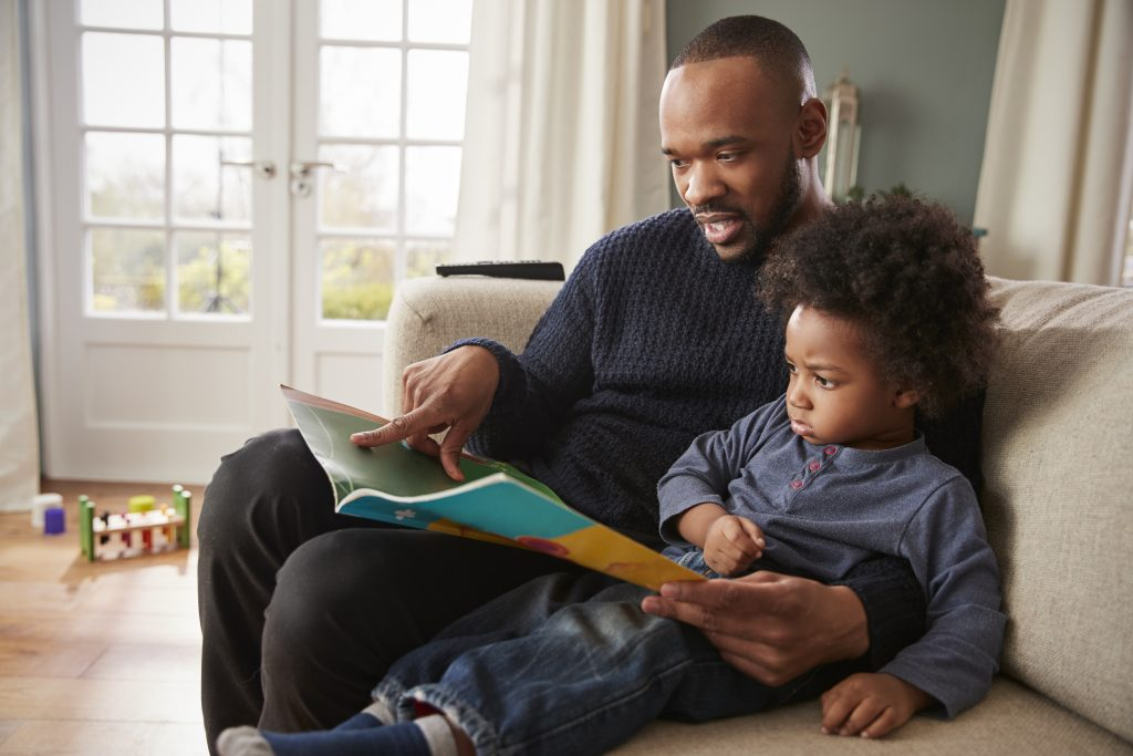 Father And Young Son Reading Book Together